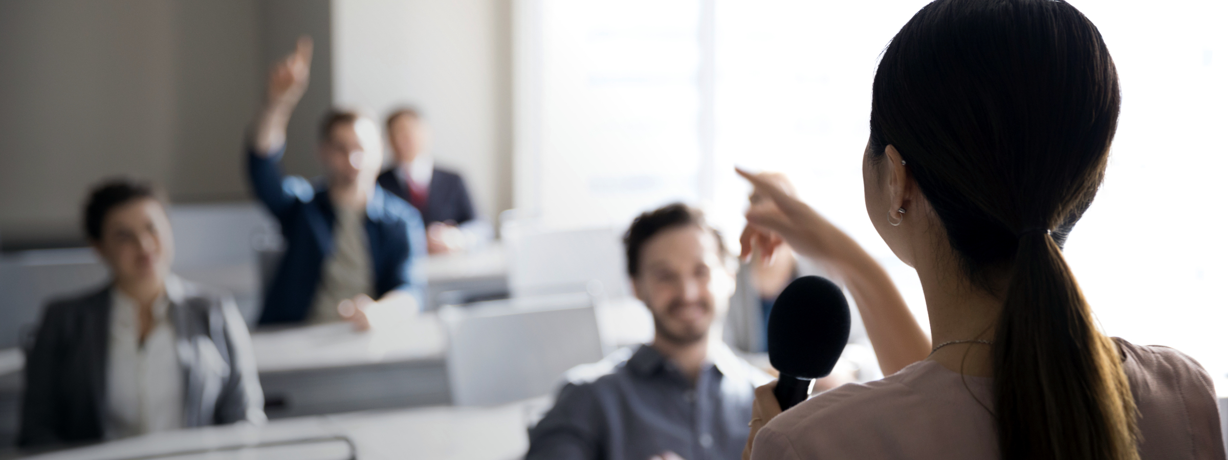 Businesswoman with microphone answering audience questions in office classroom